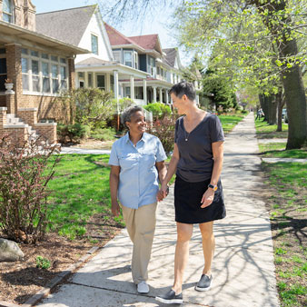Lori Lightfoot for Chicago Mayor Bio Page at home walking on sidewalk with spouse